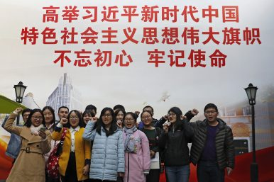 the picture is showing that a lot of peoplle taking oath in front of a banner that promoting Xi's though